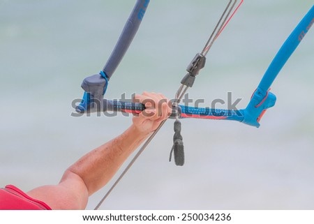 kite surfer's hand with bar isolated over sky background - stock photo