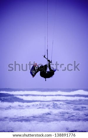 Kite surfer silhouette on blue sky background (blue tonned) - stock photo
