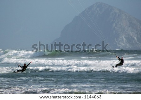 Kite surfers (kite boarder) riding the waves near Morro Bay, CA