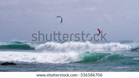 Kite-surfers riding big waves, Sal island, Cabo Verde. - stock photo