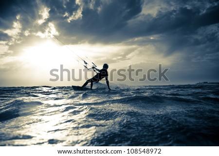 Kite surfing at sunset. - stock photo
