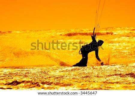 kite surfing during sunset - stock photo