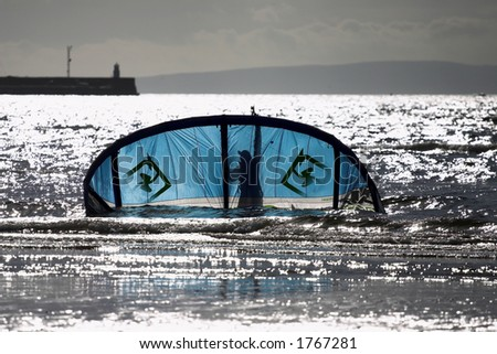Kite-surfing kite being rescued from the sea - stock photo