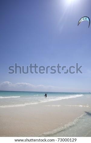 Kite surfing on tropical beach - stock photo