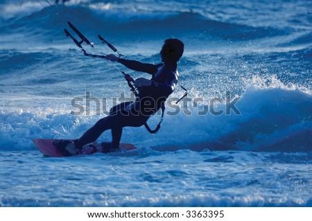 kite surfing, silhouette of sportsmen on blue - stock photo