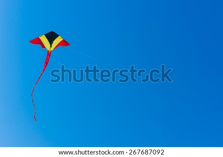 Kite triangular, yellow, red, black, flying high in the clear blue sky.