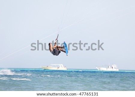 Kiteboarder enjoy surfing in blue water and jumps high in the air. - stock photo