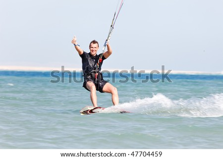 Kiteboarder enjoying surfing in blue water and showing thumbs up - stock photo