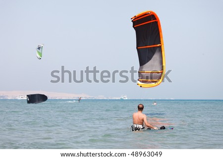 Kiteboarder lifting kite in the air. - stock photo