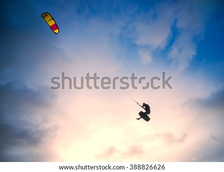 Kiteboarder performing a jump against sky at sunset  - stock photo