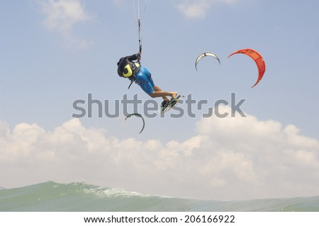 Kiteboarding in a summer day on  a Mediterranean sea coast - stock photo