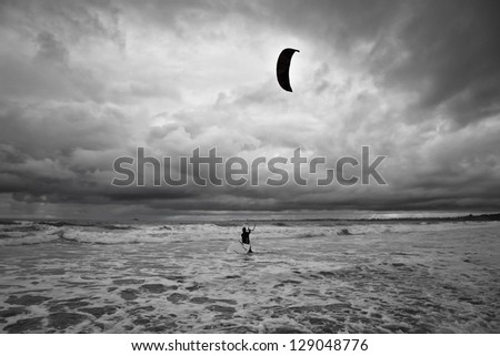 Kitesurfer gets in the water during a storm. - stock photo