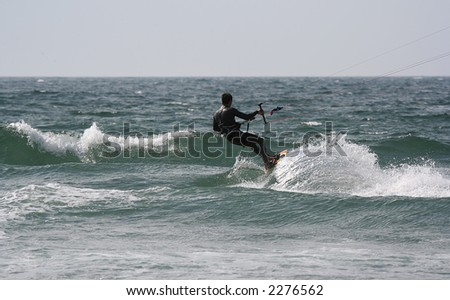 kitesurfer in the wave with a blue sky - stock photo
