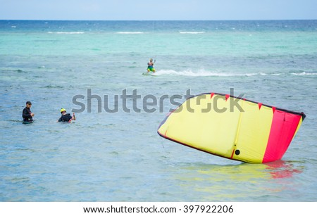 Kitesurfing instructor and female student in shallow sea waters. Woman trying to lift kite. - stock photo
