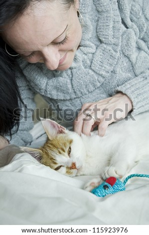 kitten with mouse and female owner on bed - stock photo