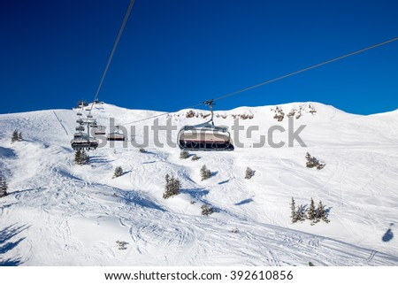 KITZBUEHEL, AUSTRIA, February 18, 2016 - Skiers on ski lift enjoying the view to foggy Alps in Austria and beautiful snowy country panorama in famous Kitzbuehel mountain ski resort