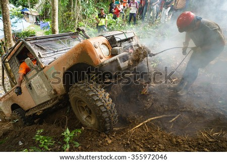 Kiulu Sabah Malaysia - Dec 20, 2015:Extreme 4X4 car passing a muddy trail of jungle route in the rainforest of Sabah Malaysian Borneo.Sabah jungle is popular for 4X4 adventures. - stock photo