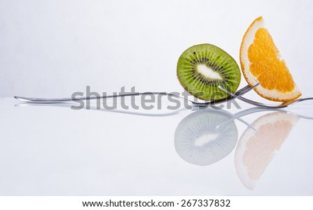 Kiwi and orange fruit slices composition on two intertwined forks - stock photo