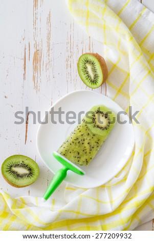 Kiwi fruit ice pop on white plate, plaid napkin, white wood background, top view - stock photo
