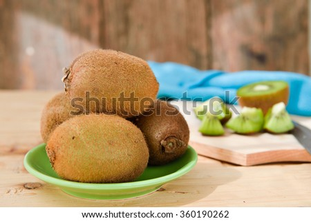 Kiwi fruit on chopping block brown wooden background - stock photo