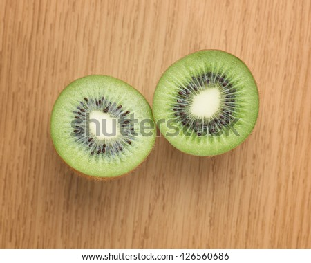 Kiwi fruits with space for text on wooden background.Ripe and half kiwi fruits. - stock photo
