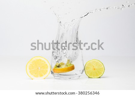 Kiwi in the glass of water, piece of lemon and lime