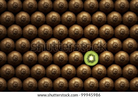 Kiwi slice amongst many whole kiwi's - stock photo
