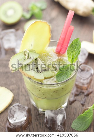 Kiwi smoothie with ginger and mint on a wooden background.