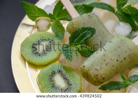 Kiwi sorbet ice cream popsicles on golden plate with ice cubes chopped kiwi slices and mint leaves on a black background. Kiwi sorbet ice cream popsicles. Horizontal. Close. - stock photo