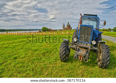 KIZHI ISLAND, RUSSIA - AUGUST 2015: Old rusty tractor on a field with monastery in background