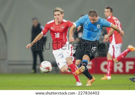 KLAGENFURT, AUSTRIA - MARCH 05, 2014: Christoph Leitgeb (#18 Austria) and Diego Perez (#15 Uruguay) fight for the ball in a friendly soccer game between Austria and Uruguay. - stock photo