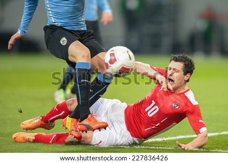 KLAGENFURT, AUSTRIA - MARCH 05, 2014: Diego Godin (#3 Uruguay) and Zlatko Junuzovic (#10 Austria) fight for the ball in a friendly soccer game between Austria and Uruguay. - stock photo