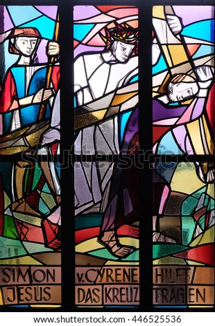 KLEINOSTHEIM, GERMANY - JUNE 08: 5th Stations of the Cross, Simon of Cyrene carries the cross, stained glass window in Saint Lawrence church in Kleinostheim, Germany on June 08, 2015. - stock photo