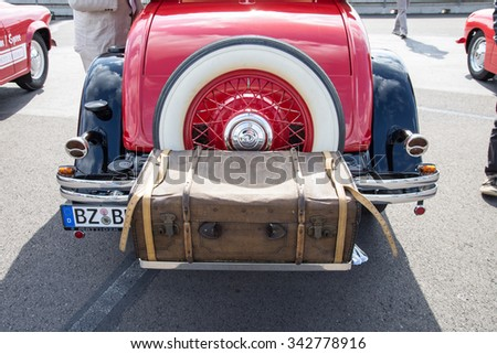 KLETTWITZ, GERMANY - September 26 2015: Suitcase placed on the trunk of a red old car. - stock photo