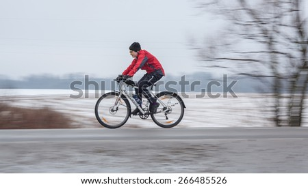 Klimovsk, Moscow Region, Russia - April 4th, 2015: Moscow cycling club Caravan event - 200km brevet(randonneuring, audax). Woman riding his bike, panning shot. The temperature is +4 celcius and the
