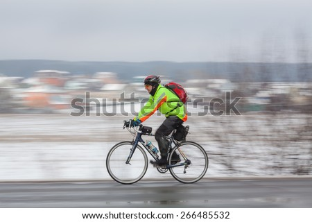 Klimovsk, Moscow Region, Russia - April 4th, 2015: Moscow cycling club Caravan event - 200km brevet(randonneuring, audax). Man riding his bike. The temperature is +4 celcius and the snow laying after