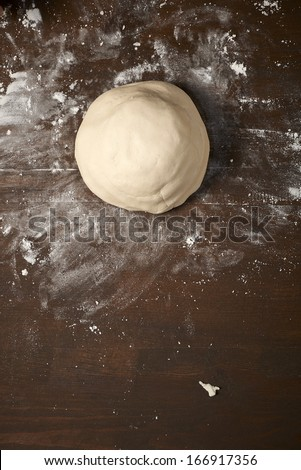 knead dough on wooden table, is ready - stock photo
