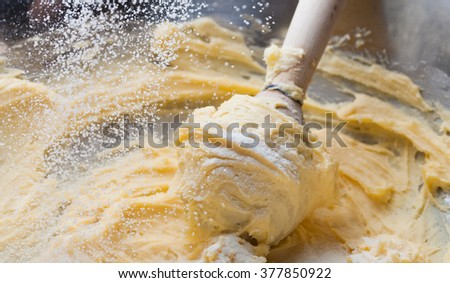 Kneading dough in mixing bowl, close up butter and flour - stock photo