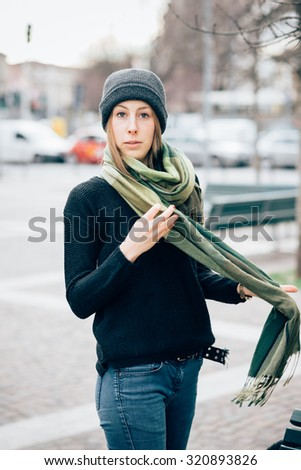 Knee figure of young beautiful hipster sporty blonde woman posing in the city, wearing a scarf, looking in camera, pensive - wearing black sweater, blue jeans and a hat