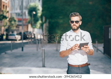 Knee figure of young handsome bearded businessman holding a tablet, looking over wearing sunglasses - technology, business, work concept, copy space left - stock photo