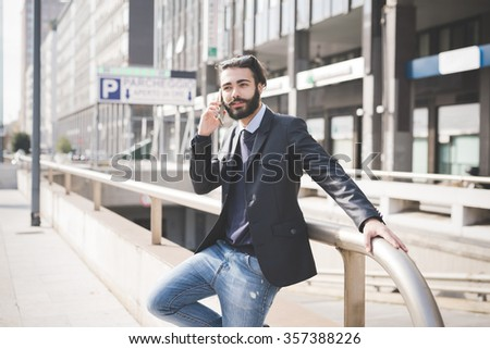 Knee figure of young handsome black hair caucasian modern businessman leaning on a pole in the city backlight, using smartphone - business, working concept