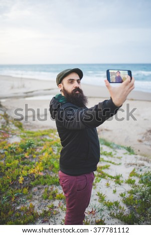 Knee figure of young handsome caucasian bearded man holding a smartphone taking a selfie on the beach - social network, communication, vanity concept - stock photo