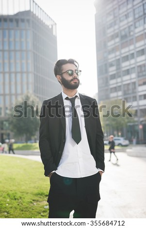 Knee figure of young handsome caucasian black hair modern businessman posing in the city, overlooking left, hands in pocket, serious - working, business, successful concept - stock photo