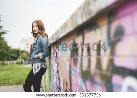 Knee figure of young handsome caucasian blonde straight hair woman posing leaning against a wall, hands in pocket, looking downward, pensive - thoughtful, serious concept - stock photo
