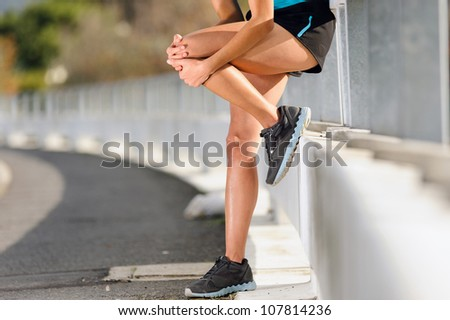knee injury for athlete runner. woman in pain after hurting her leg while training for fitness marathon - stock photo