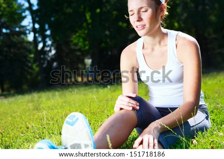 Knee injury for young woman athlete runner. - stock photo
