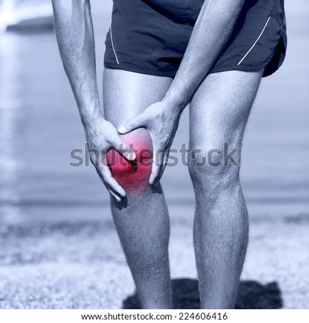 Knee Injury - sports running knee injuries on man. Male runner with pain from sprain knee. Close up of legs, muscle and knee outdoors. - stock photo