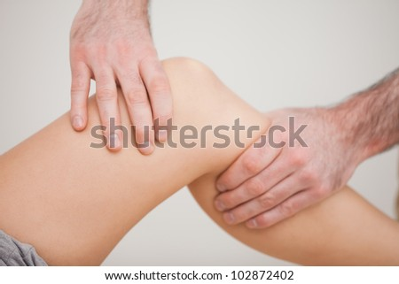 Knee of a patient being touched by a practitioner in a room - stock photo