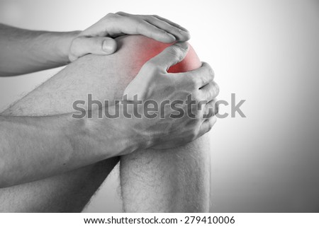 Knee pain in men on gray background - stock photo