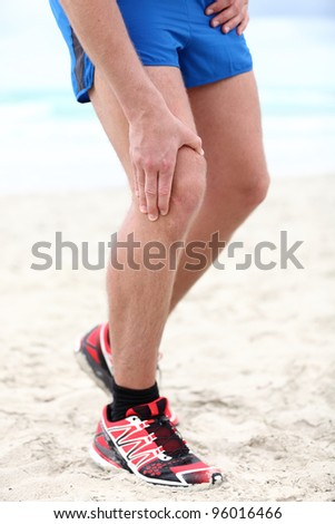 Knee pain - runner injury. Pain in knee joints in man running on beach. - stock photo